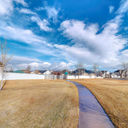 Square Paved pathway on grassy ground leading to houses on a residential neighborhood. Scenic landscape on a sunny day with blue sky and puffy clouds overhead.