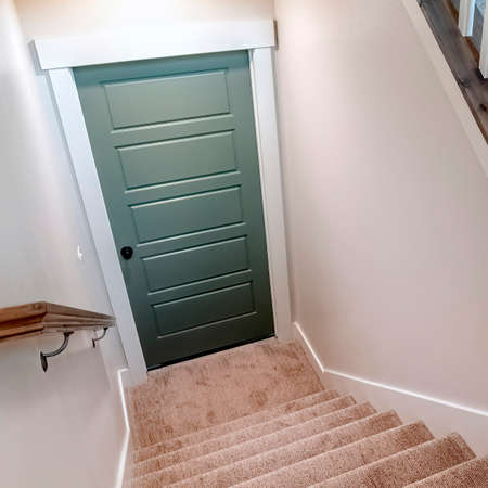 Square Carpeted U shaped staircase that leads down to the basement door of a home. The stairs have brown handrail that is supported by white balusters. Banque d'images