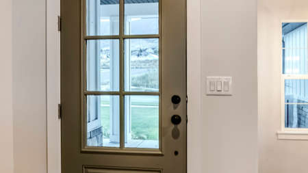 Panorama Hinged front door with glass pane viewed from interior of home with wood floor. Multiple rocker light switch is installed on the wall beside the doorframe. Standard-Bild