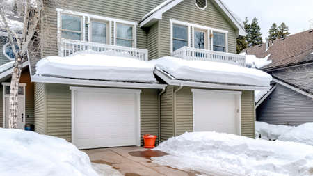 Panorama Facade of home with snowy driveways in front of two car garage viewed in winter. Pitched roof, gray wall siding, and balconies can also be seen at the exterior of this house.