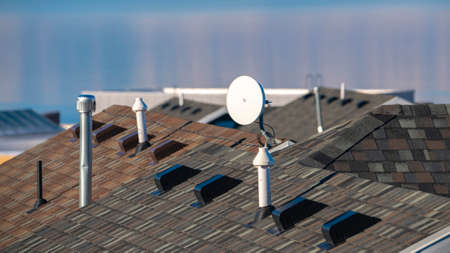 Panorama frame Television satellite dish mounted on a tiled house roof with selective focus and Utah Lake in the background Stock Photo