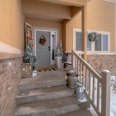 Square frame Wet stairs at home entrance leading to front door with christmas tree and wreath. The yard of the house is covered with snow on this cold winter season.