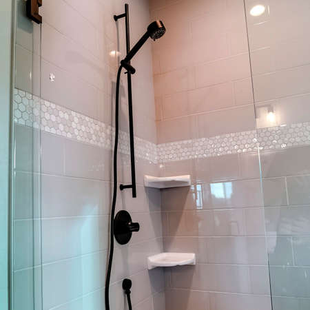 Square Black round shower head on tile wall of shower stall with hinged glass door. Soap holders are also installed at the corner of the bathroom wall.