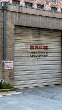 Vertical crop Corrugated metal garage door of an old brick building with No Parking sign. Entrance to the garage of a building with signages at the exterior wall. Stock Photo