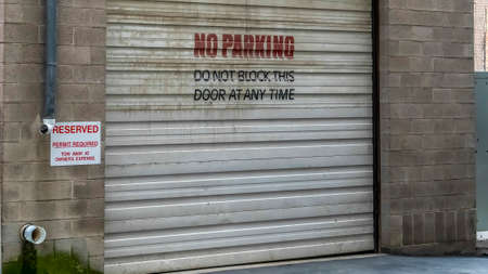 Panorama Corrugated metal garage door of an old brick building with No Parking sign. Entrance to the garage of a building with signages at the exterior wall. Stock Photo