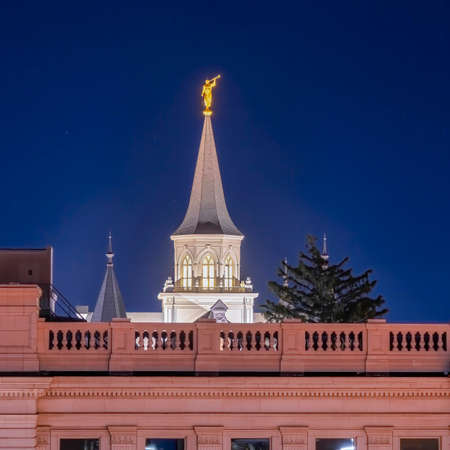 Square frame Provo City Center Temple with statue of angel and spire against blue evening sky. Exterior view of the temple of The Church of Jesus Christ of Latter-day Saints in Utah at night.