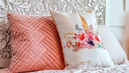 Panorama Fluffy pillows against decorative headboard of single bed against panelled wall. Bedroom interior with an empty bed covered with pink and floral beddings.
