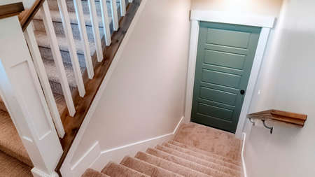 Panorama Carpeted U shaped staircase that leads down to the basement door of a home. The stairs have brown handrail that is supported by white balusters. Banque d'images