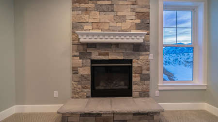 Panorama frame Fire insert in a feature stone brick wall and chimney in a modern unfurnished living room in a house with window to a winter landscape