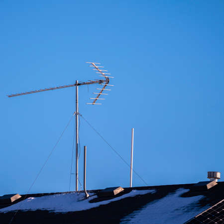 Square Communications antenna mounted on a rooftop with remnants of winter snow against a blue sky