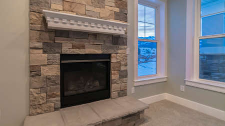 Panorama crop Modern fireplace and decorative shelf against stone brick accent wall of home