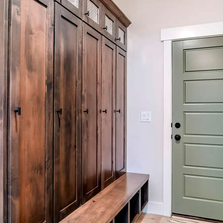 Square Panelled fire door with black knobs and lock adjacent to a tall vintage cabinet. Interior of a home with wall paneling and runner rug on the floor.