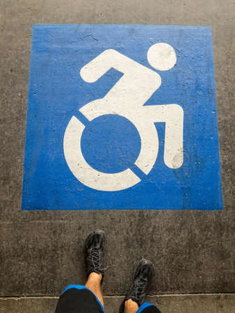 Handicapped sign on a parking space with feet of a man wearing black shoes