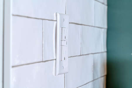 Home interior with close up view of a grounded outlet installed on the tile wall