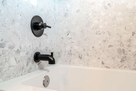 Close up of rectangular bathtub and wall mounted faucet with single lever handle