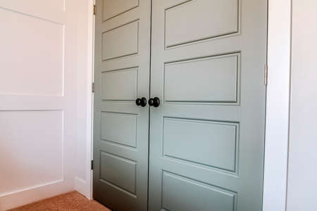 Double doors with hinges and black round doorknob at the bedroom entrance