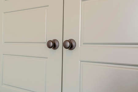 Wooden panelled double doors with shiny round doorknobs at the bedroom entrance