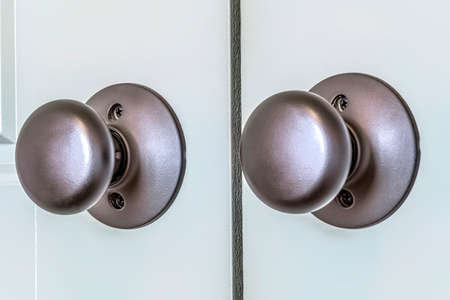 Shiny round doorknobs of a wooden double door at the entrance of a bedroom