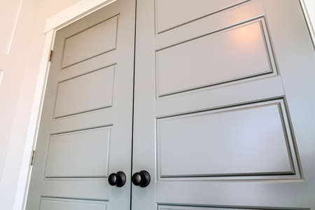 Hinged interior double doors with panelled design and shiny round doorknobs