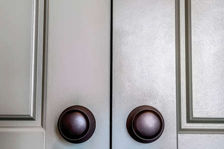 Shiny round black doorknobs installed on the wooden panelled double doors