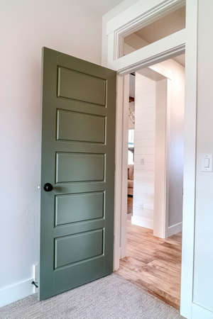 Open bedroom door with transom window looking out to the living area and hallway Фото со стока