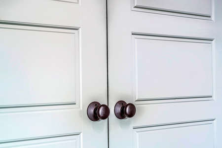 Hinged wooden interior double doors with panelled design and round doorknobs