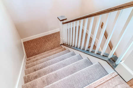 Interior staircase with U shaped design wooden handrail and carpet on treads