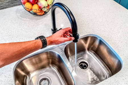 Man holding black curved faucet with water running down the double basin sink