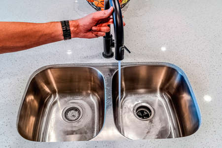 Male hand holding the black spout of a faucet with water running down the sink