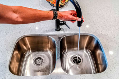 Man holding black faucet with water running down the drain of undermount sink