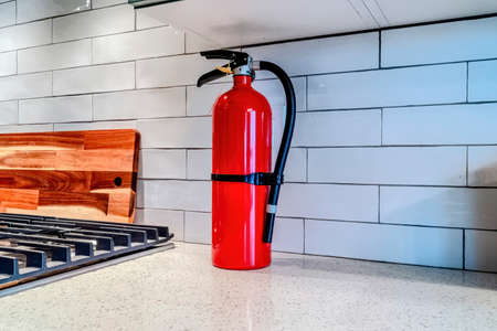 Bright red fire extinguisher against white tile backsplash inside home kitchen Фото со стока