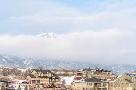 Houses on a scenic winter setting with Wasatch Mountains and cloudy sky view Фото со стока