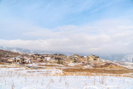 Neighborhood on a winter setting with Wasatch Mountains and cloudy sky views