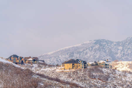 Nature and residential landscape on a snowy winter day with cloudy sky overhead