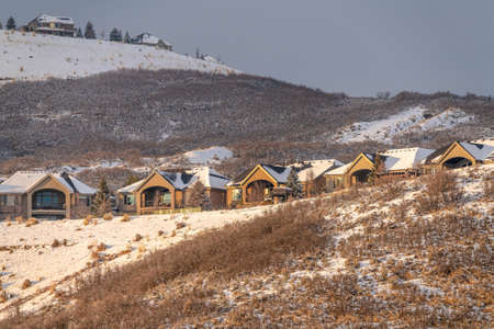 Facade of identical homes built on the slope of mountain with snow in winter Фото со стока