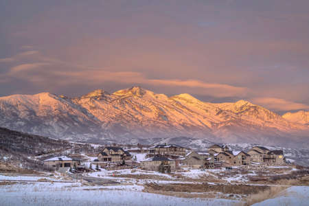 Winter landscape of Wasatch Mountains and houses in Utah Valley at sunset