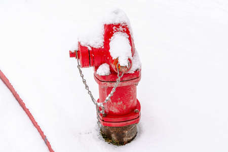 Old fire hydrant with bright red paint on a snowy and frosty winter setting