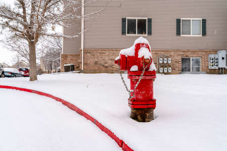 Bright red fire hydrant on the roadside of community covered with snow in winter