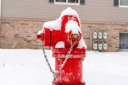 Close up of a bright red fire hydrant against snow and building in winter Фото со стока