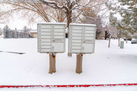 Cluster mailbox on snow covered roadside of residential neighborhood in winter Фото со стока