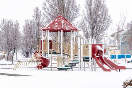 Park on a scenic neighborhood with colorful playground on a snowy winter setting Фото со стока