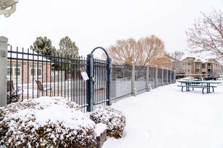 Building and swimming pool inside gated property on a snowy town in winter Фото со стока