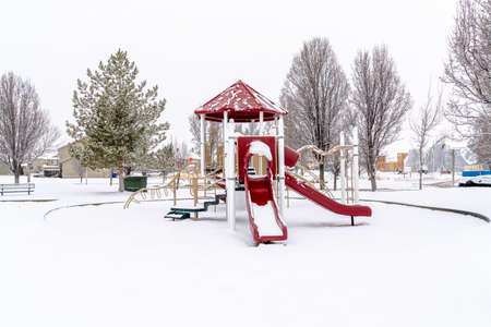 Park on neighborhood with colorful childrens playground on snowy winter setting Фото со стока