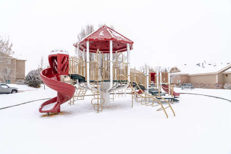 Playground with red slides of a neighborhood park on a scenic winter landscape Фото со стока
