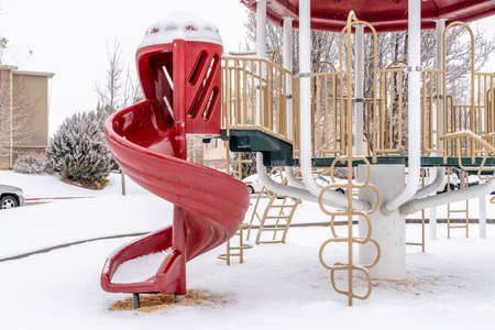 Curvy red slide of a neighborhood playground on a scenic snowy winter setting Фото со стока