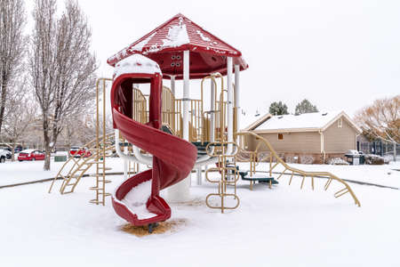 Childrens playground with curvy red slide amid houses on a frosty winter setting Фото со стока