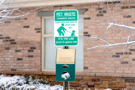 Pet waste sign with dog poop bags reminding people to clean up after their pets
