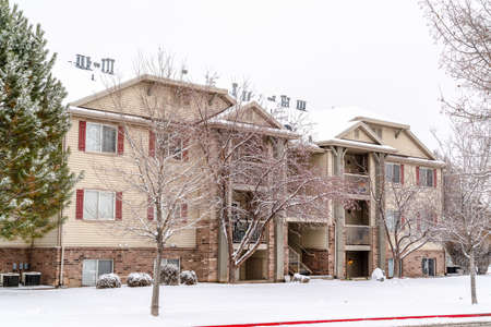 Facade of three story apartment with snow covered yard and roof in winter