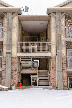 Entrance to a housing complex with flight of staits and balconies at the facade