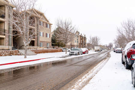 Wet road along apartments on snow covered neighborhood on a cloudy winter day Фото со стока